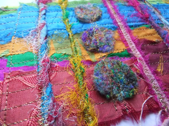 Sample 5 left detail - showing felt circles made from the shredded silk fibre and sari ribbon yarn on sari ribbon.