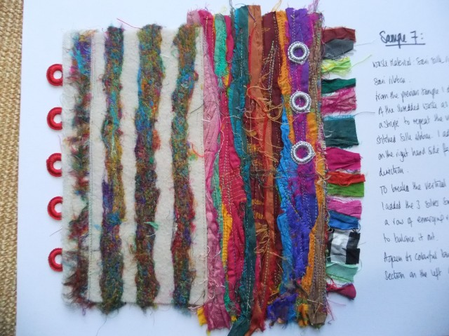 "Sample 7 - Final sample. Interestingly I took a step back with this one and went with the ""less is more"" approach as it was all becoming quite vibrant, as you might expect with the sari silk fabrics. I arrived at this one by taking elements from some ot the others. I like the contrast between the needle felted more muted strips and the vibrant all singing and dancing stripes on the right. The fringe on the right is a nice detail and then to balance it up and as a nod towards Indian tradition I used sashima rings without the mirrors."