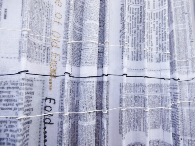 A vertical panel which has been hand pleated on one side and rolled on the other combines several elements of the English Language by using a digital print of patch worked dictionary pages and machine embroidered textile related words.